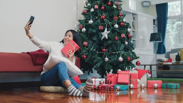 Aziatische vrouwen vieren kerstfestival. de vrouwelijke tiener ontspant gelukkige holdingsgift en thuis gebruikend smartphone selfie met kerstboom geniet de vakantie van de kerstmiswinter in woonkamer.