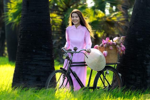 Aziatische vrouwen vietnam is meisje trolley fiets naar de winkel na de lotusbloem mand.