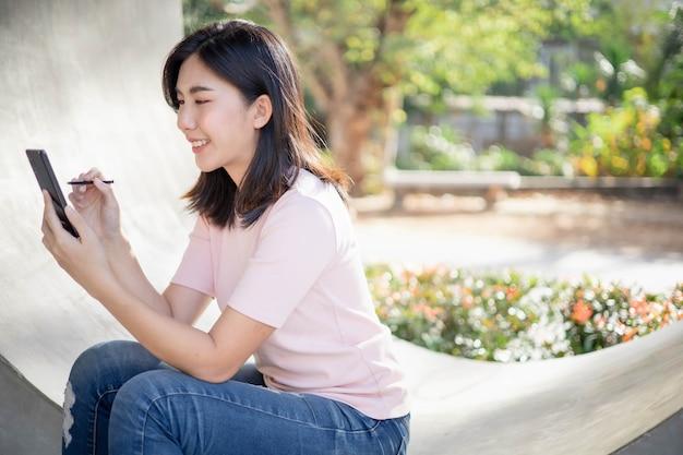 Aziatische vrouwen werken en luisteren naar muziek op mobiele telefoons.