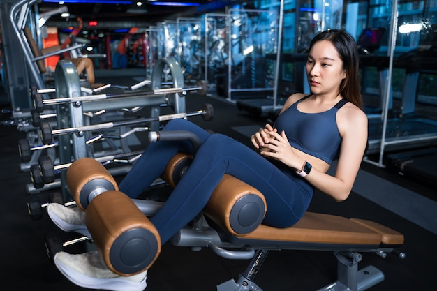Aziatische vrouwen zijn vastbesloten om hun buikspieren te trainen met een sit-up pose met een sit-up device.