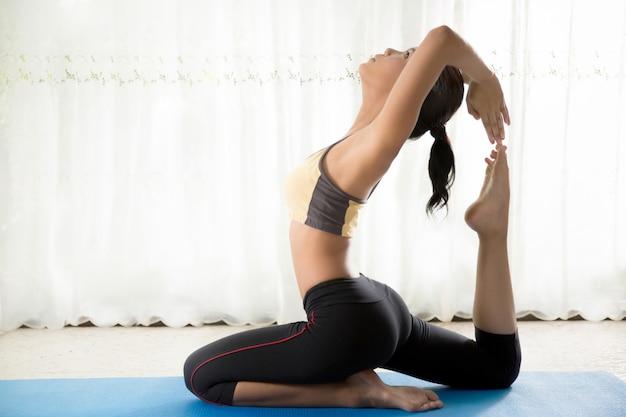 Aziatische vrouwen zijn yoga-oefeningen thuis