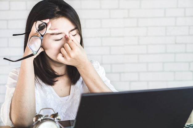 Aziatische vrouwenarbeider die aan oogspanning lijden