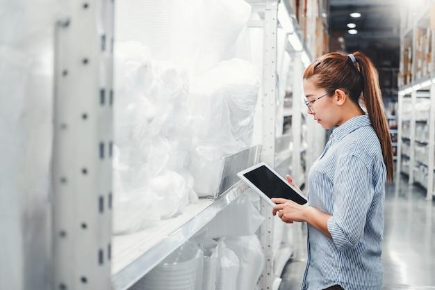 Aziatische vrouwenarbeider die met digitale tablet werken die dozen controleren
