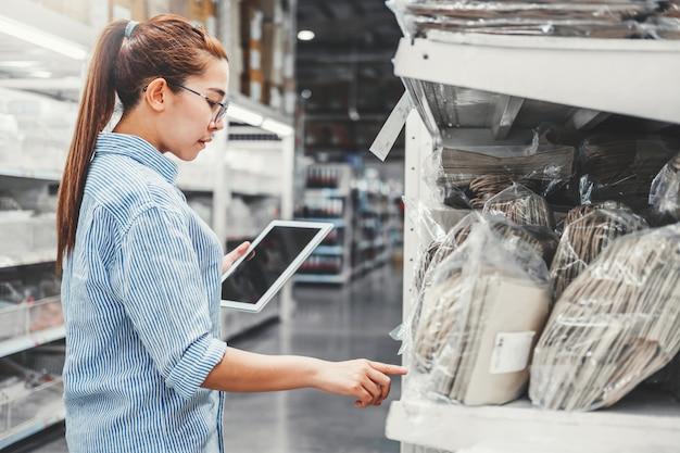 Aziatische vrouwenarbeider die met digitale tablet werkt