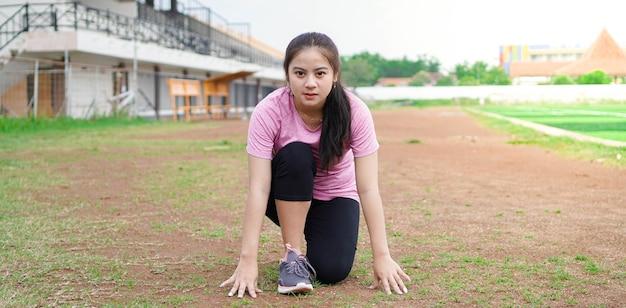 Aziatische vrouwenatleet die zich klaarmaakt om op het goede spoor te gaan lopen