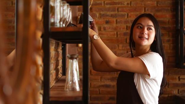 Aziatische vrouwenbarista die glazen schikken bij café