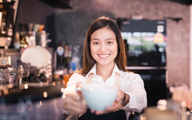 Aziatische vrouwenbarista die met een kop van koffie in haar hand glimlachen