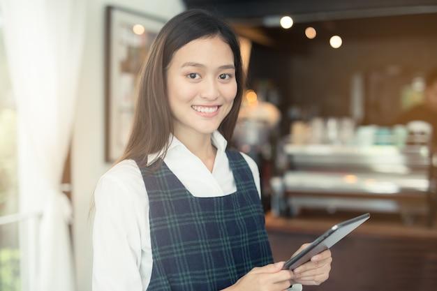 Aziatische vrouwenbarista die met tablet in haar hand glimlachen
