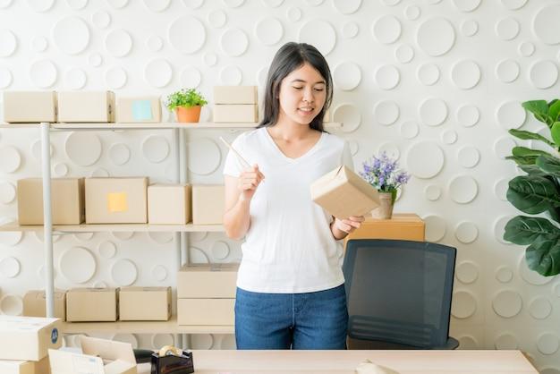 Aziatische vrouwenbedrijfseigenaar die thuis met verpakkingsdoos aan werkplaats werken