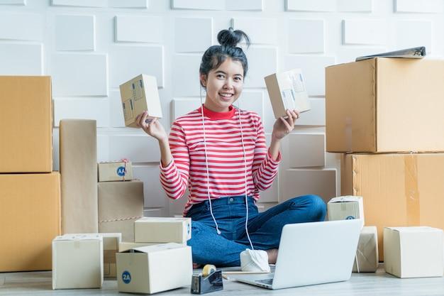 Aziatische vrouwenbedrijfseigenaar die thuis met verpakkingsdoos werken op werkplaats