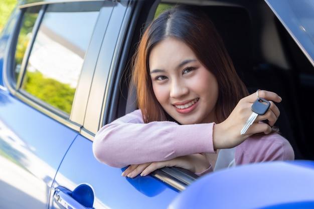 Aziatische vrouwenbestuurder die en nieuwe autosleutels glimlacht toont en in de auto zit
