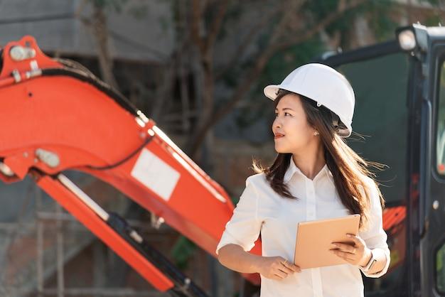 Aziatische vrouwenburgbouwer met witte het bezoekbouwwerf van de veiligheidshelm.
