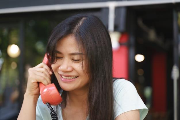 Aziatische vrouwenglimlach en het lachen op telefoon
