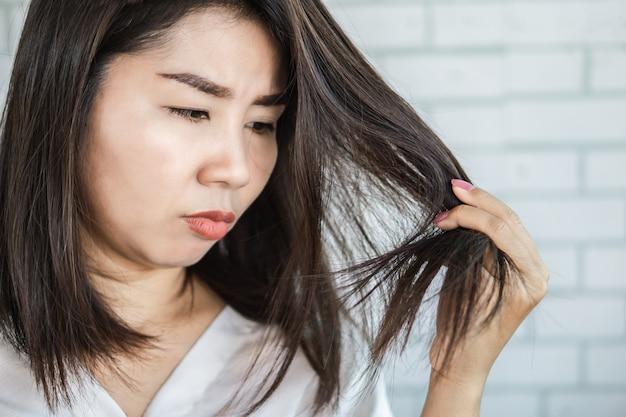 Aziatische vrouwenhand die beschadigd gespleten haarpuntenhaar houden