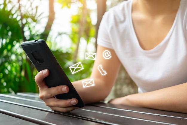 Aziatische vrouwenhand die smartphone gebruiken om met e-mail te contacteren