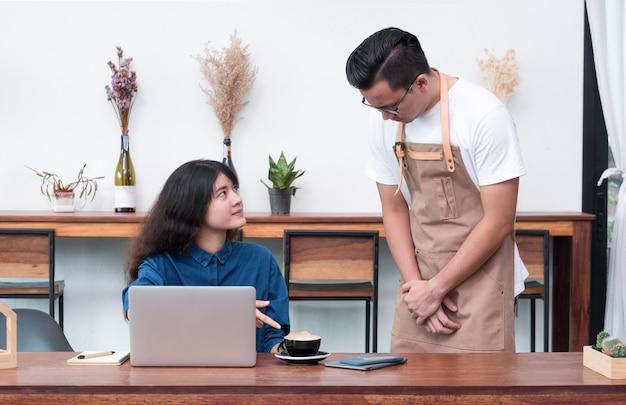 Aziatische vrouwenklant die aan kelner over voedsel in koffierestaurant klagen