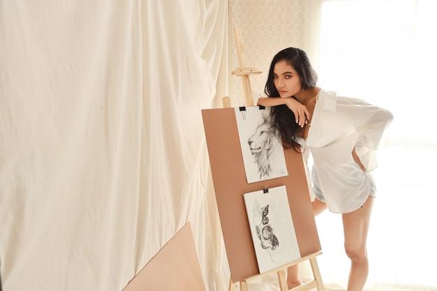 Aziatische vrouwenkunstenaar die in wit overhemd iets denkt terwijl het trekken van beeld met potlood (het concept van de vrouwenlevensstijl)