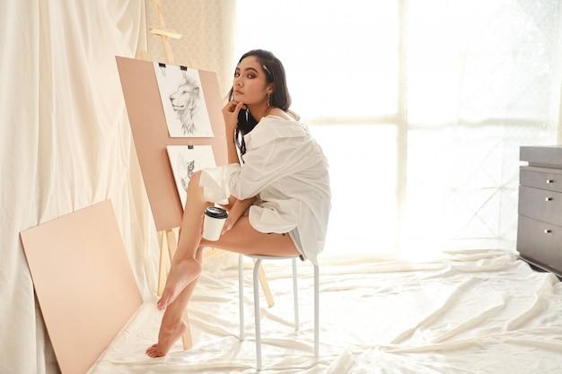 Aziatische vrouwenkunstenaar in wit overhemd die een onderbreking nemen terwijl het trekken van beeld met potlood (het concept van de vrouwenlevensstijl)