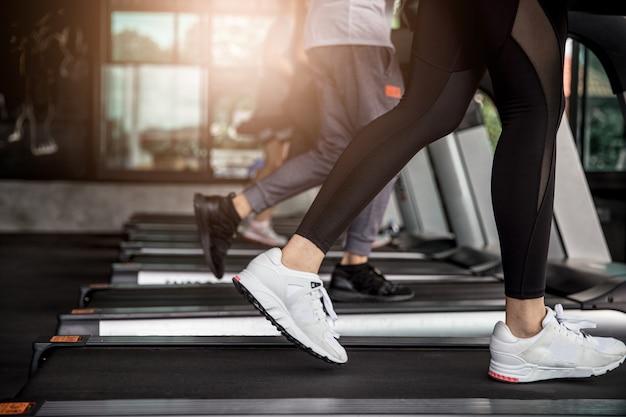 Aziatische vrouwenoefening die op machinetreadmill lopen