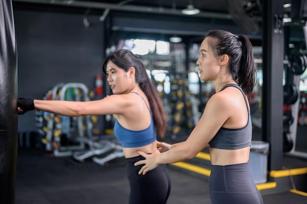 Aziatische vrouwenoefening en levensstijl bij geschiktheidsgymnastiek. sportieve vrouwentraining en boksen met trainer. wellness en gezond voor bodybuilding.