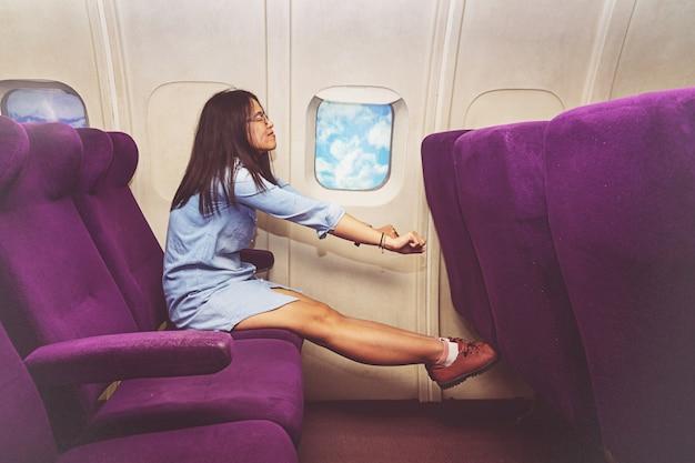 Aziatische vrouwenpassagier het ontspannen bij de commerciële klasse van vliegtuig