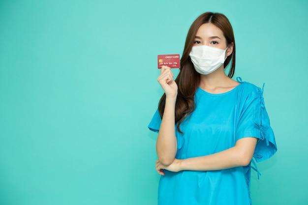 Aziatische vrouwenpatiënt die creditcard toont en beschermend medisch masker draagt