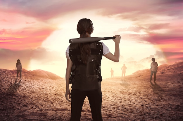 Aziatische vrouwenpolitie met honkbalknuppel in zijn schouder die zombieën bekijken