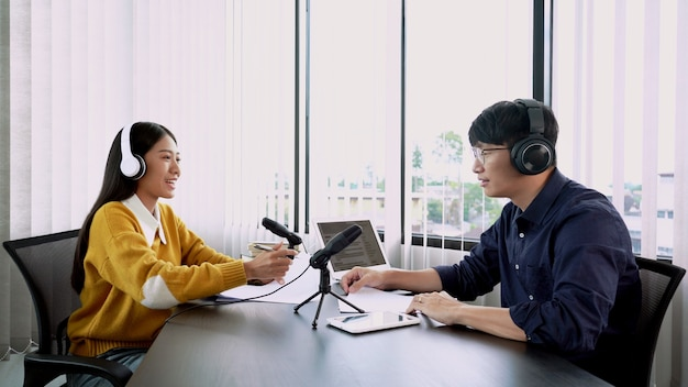 Aziatische vrouwenradiopresentatoren gebaren naar microfoon tijdens het interviewen van een mannelijke gast in een radiostation tijdens een show voor radio live in de studio.