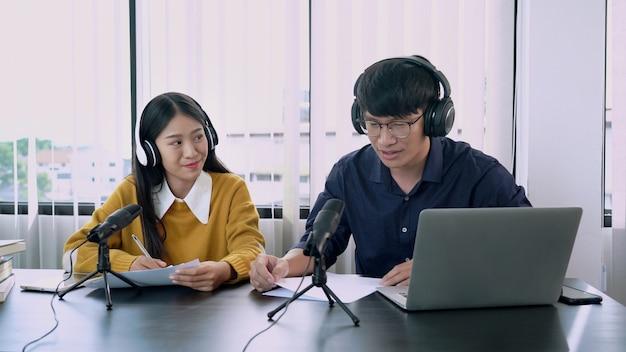 Aziatische vrouwenradiopresentatoren gebaren naar microfoon tijdens het interviewen van een mannelijke gast in het radiostation Premium Foto