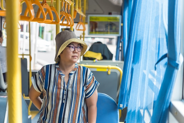 Aziatische vrouwenreis door passagiersbus in stad