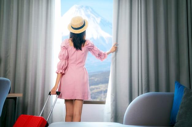 Aziatische vrouwenreiziger arriveert in de kamer in het hotel en opent het gordijn om te genieten van het uitzicht op fuji