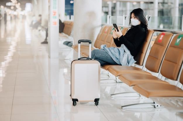Aziatische vrouwenreiziger die gezichtsmasker draagt dat op sociale afstandsstoel zit
