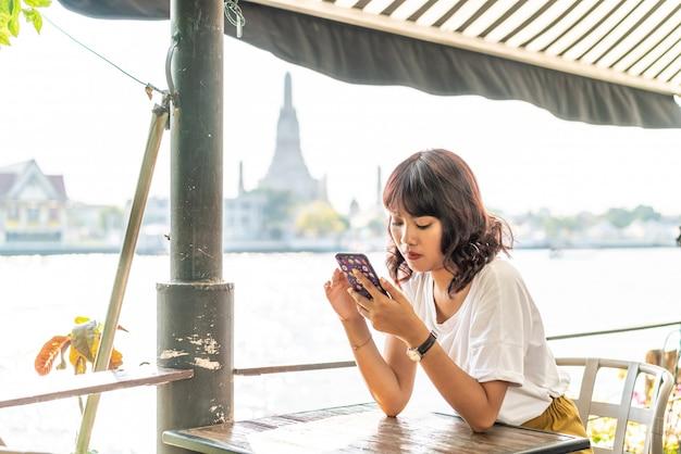 Aziatische vrouwenreiziger die haar telefoon in koffie met behulp van