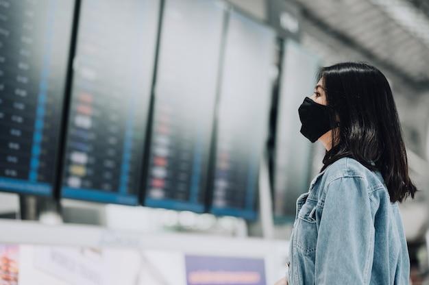 Aziatische vrouwenreiziger die masker draagt dat de vertoning van het vluchtinformatiebord kijkt