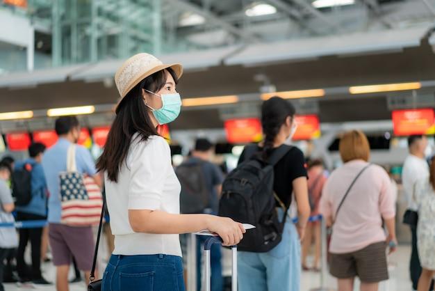 Aziatische vrouwenreiziger die masker dragen bij klantencontrole van de teller van de luchtvaartlijndienst