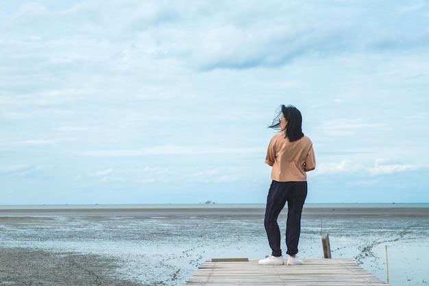 Aziatische vrouwenreiziger die zich bij zeegezicht op houten brug met blauwe hemel en oceaan bij achtergrond bevinden