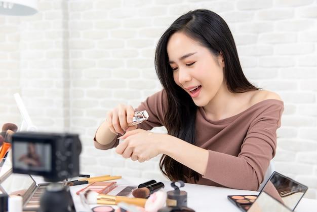 Aziatische vrouwenschoonheid vlogger die kosmetisch overzicht op sociale media uitzendt