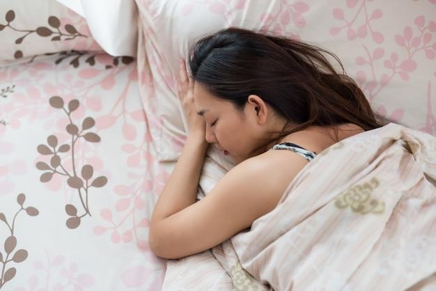Aziatische vrouwenslaap op bed