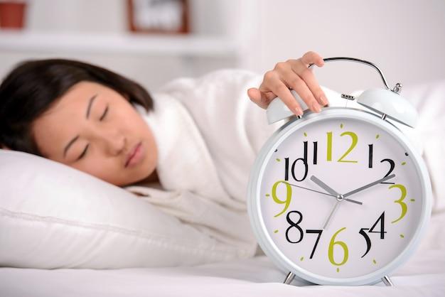 Aziatische vrouwenslaap op het bed thuis.