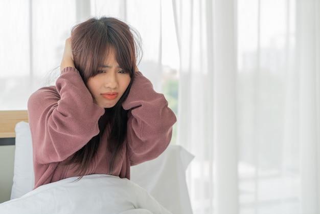 Aziatische vrouwenspanning en ernstig op bed