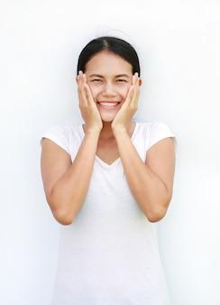 Aziatische vrouwent-shirt die en zich wat betreft haar wang met glimlach op witte achtergrond bevinden