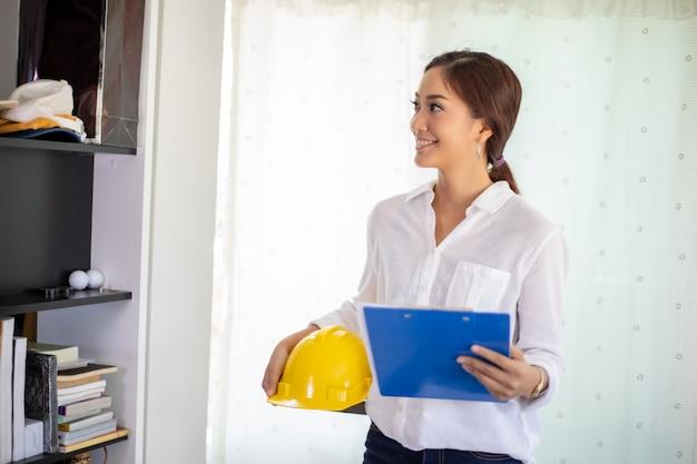Aziatische vrouwentechniek die en blauwdrukken inspecteren werken en houden op kantoor. zij glimlacht gelukkig voor het werk