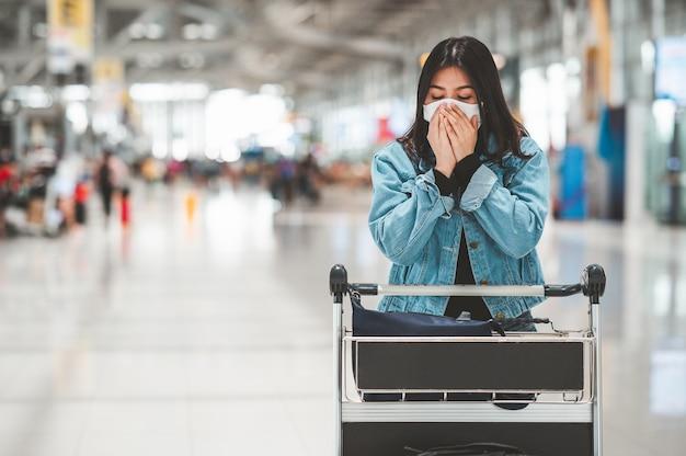 Aziatische vrouwentoerist die beschermend gezichtsmasker met bagagekarretje draagt
