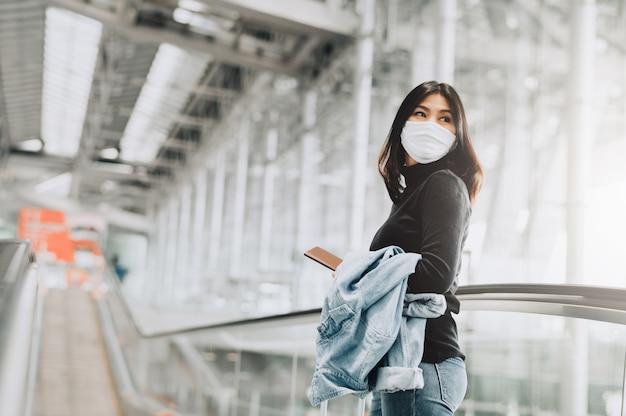 Aziatische vrouwentoerist die de holdingspaspoort van het gezichtsmasker draagt