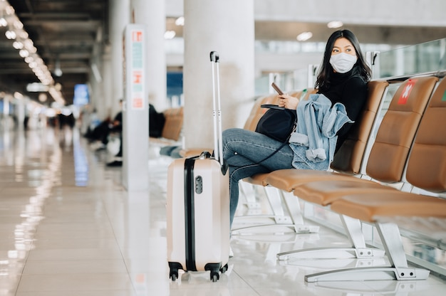 Aziatische vrouwentoerist die gezichtsmasker draagt dat op sociale afstandsstoel zit