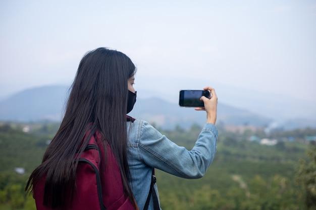 Aziatische vrouwentoerist die gezichtsmasker draagt die telefoon bekijkt