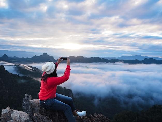 Aziatische vrouwentoerist die op de rots bij de bovenkant van berg zitten en de hemel van de fotozonsopgang nemen.