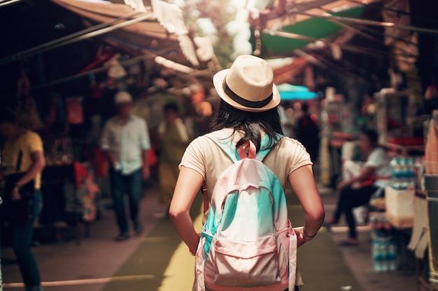 Aziatische vrouwentoerist met rugzakreis in markt van thailand