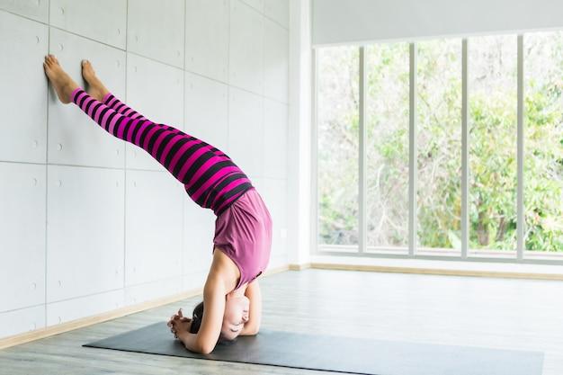 Aziatische vrouwentraining die yoga uitoefenen die op roze kleren en praktijkmeditatie wordt gezet