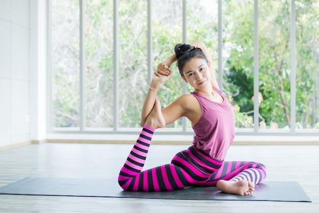Aziatische vrouwentraining die yoga uitoefenen die op roze kleren zetten en de levensstijl van de meditatiewellness en het concept van de gezondheidsgeschiktheid in een gymnastiek uitoefenen